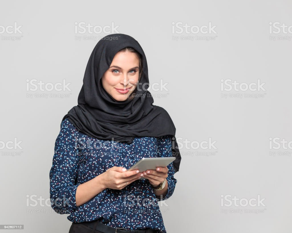 Cheerful young muslim woman holding digital tablet Portrait of cheerful young woman holding digital tablet. Businesswoman in hijab looking at camera against grey background. 20-29 Years Stock Photo