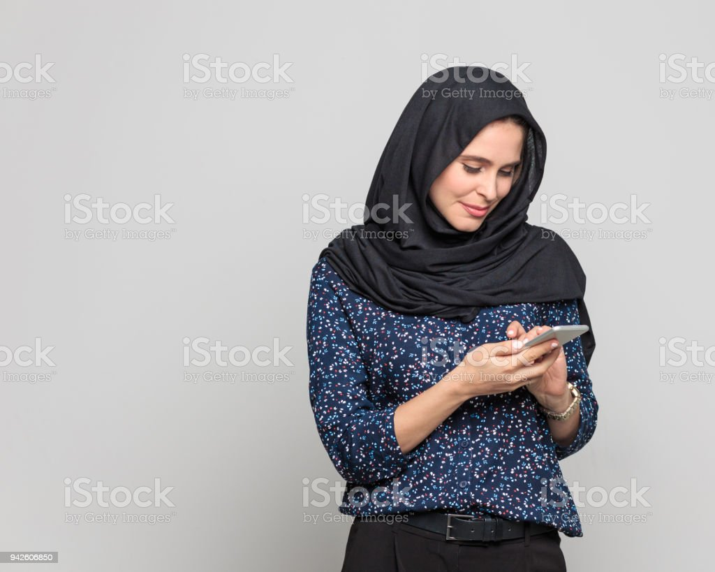 Cheerful young muslim woman using smart phone Portrait of cheerful young woman holding smart phone. Businesswoman in hijab using mobile phone against grey background. 20-29 Years Stock Photo
