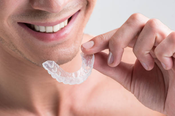 Cheerful young nude guy is holding plastic transparent brace stock photo