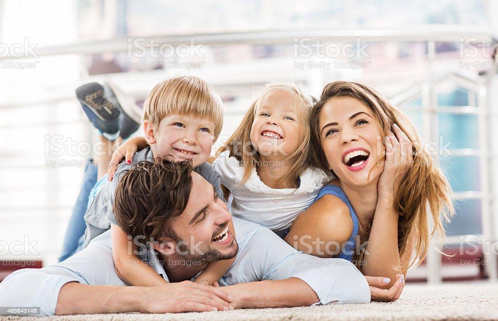 Fröhlich junge Eltern und Kinder zu Hause fühlen. – Foto