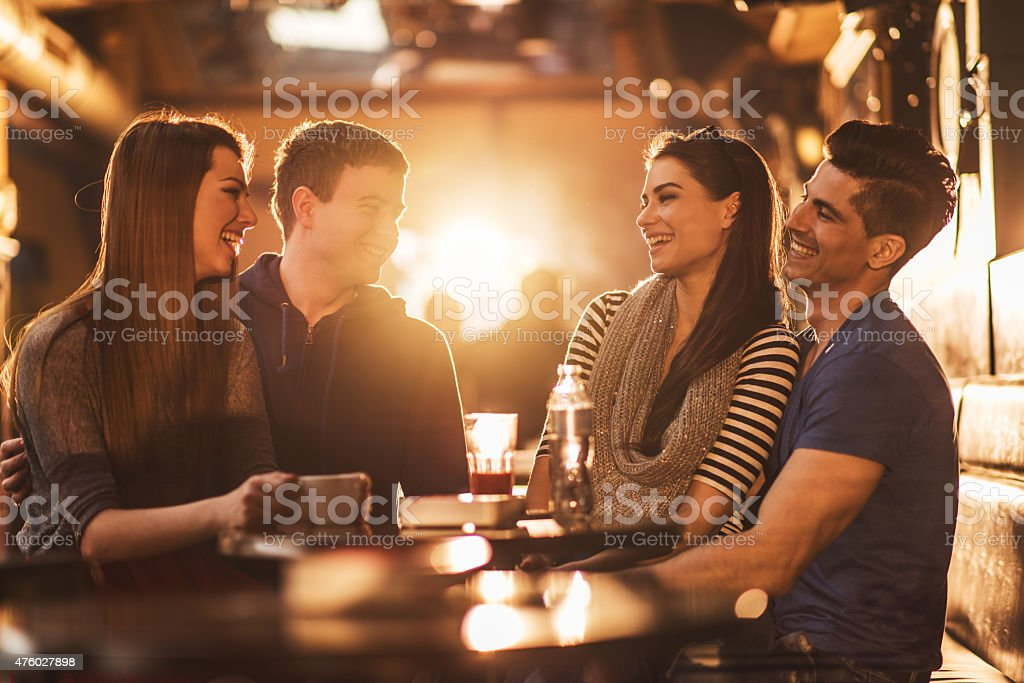Cheerful young people communicating and enjoying in a cafe. stock photo
