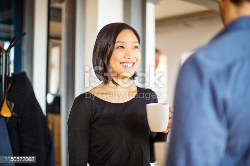 Smiling asian businesswoman with a cup of coffee talking male colleague. Two cheerful young people holding coffee cups and talking while standing in office.