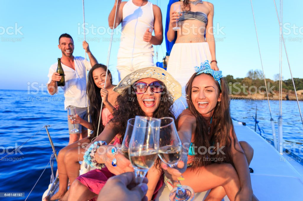 Cheerful young people having party on yacht and drinking wine stock photo