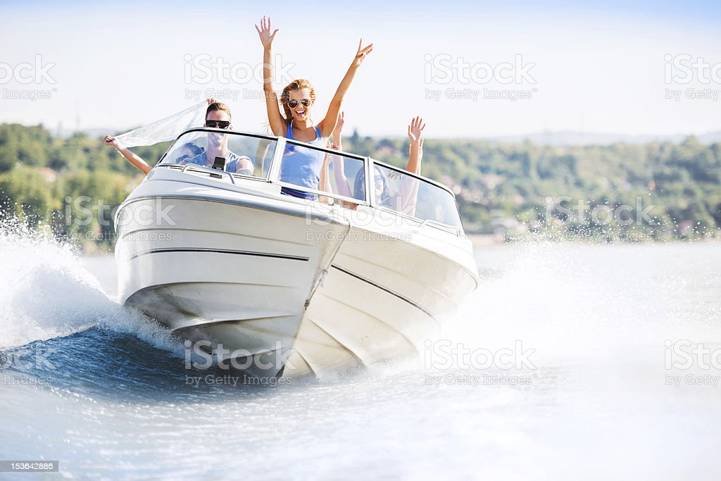 Cheerful young people riding in a speedboat bildbanksfoto