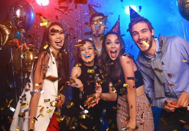 jóvenes alegres se duchó con confeti en una fiesta del club. - fiesta fotografías e imágenes de stock