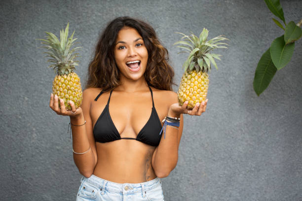 Cheerful Young Pretty Woman In Bra With Pineapples stock photo