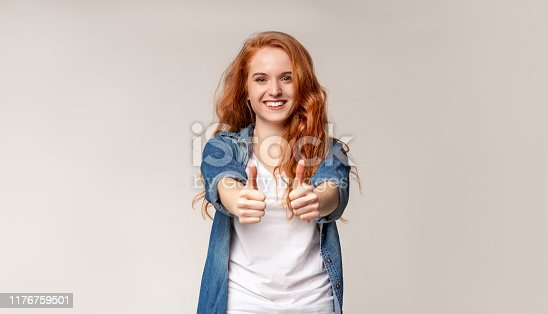 I like it. Cheerful young redhead girl showing thumb up and smiling at camera. Panorama with copy space