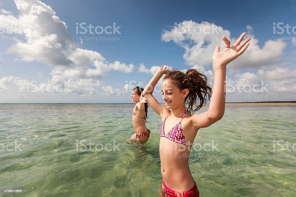 Cheerful Young Sisters Playing in Natural Pool in Sunny Beach stock photo