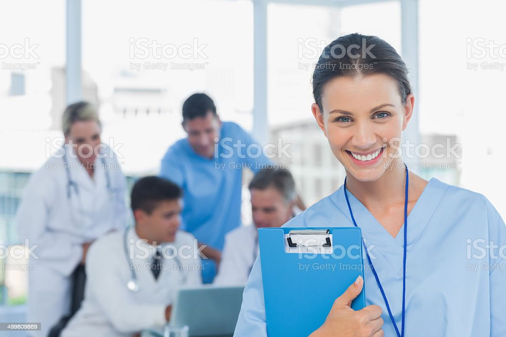 Cheerful young surgeon posing with colleagues in background stock photo