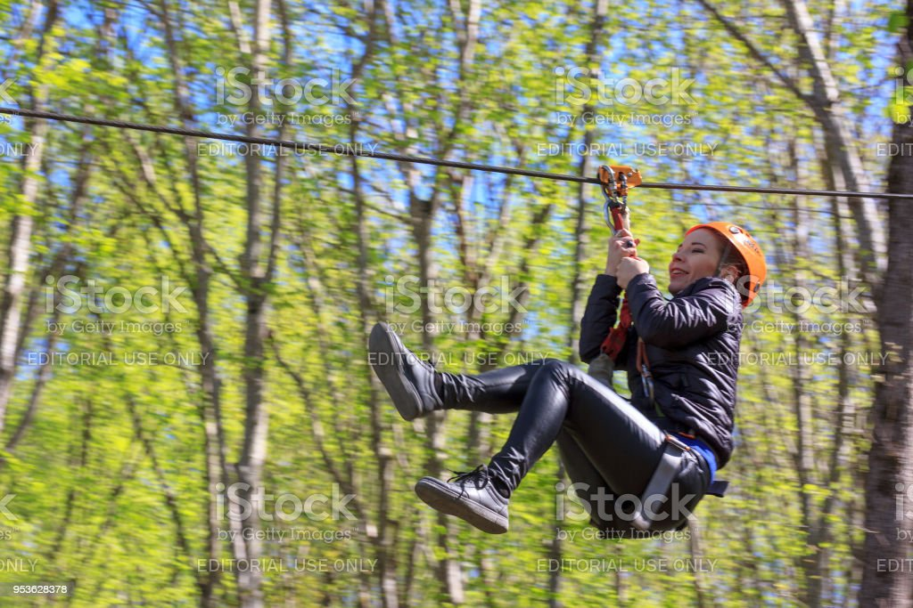 cheerful young tourist girl descends on Zipline above the gorge of the river Mishoko in the mountains of Adygea in the Western Caucasus stock photo