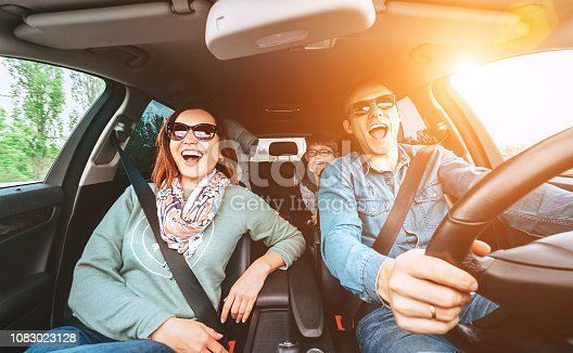 istock Cheerful young traditional family has a long auto journey and singing aloud the favorite song together.  Safety riding car concept wide angle view image. 1083023128