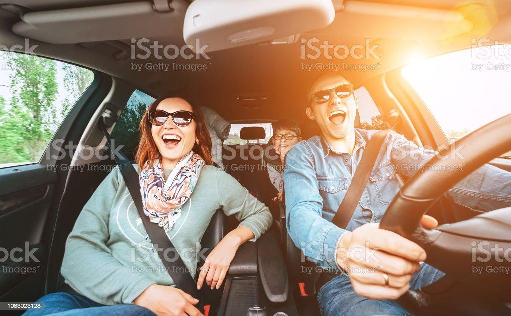 Fröhliche junge traditionelle Familie hat eine lange Auto-Reise und laut dem Lieblingslied singen.  Sicherheit Reiten Auto Konzept Weitwinkel Bild anzeigen. – Foto