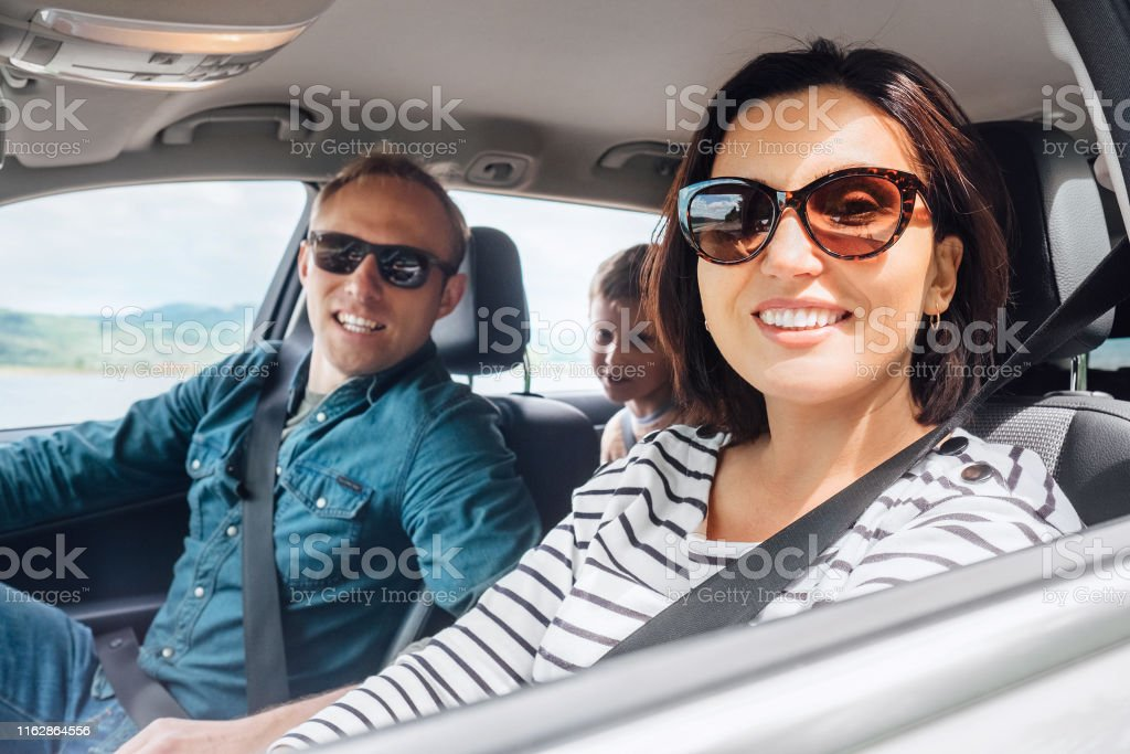 Cheerful young traditional family has a long auto journey and smiling...