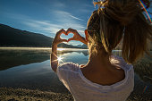 istock Cheerful young woman by the lake loving nature 495622306
