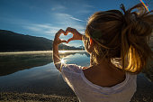 istock Cheerful young woman by the lake making heart shape frame 495736600