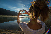 istock Cheerful young woman by the lake making heart shape frame 495988594