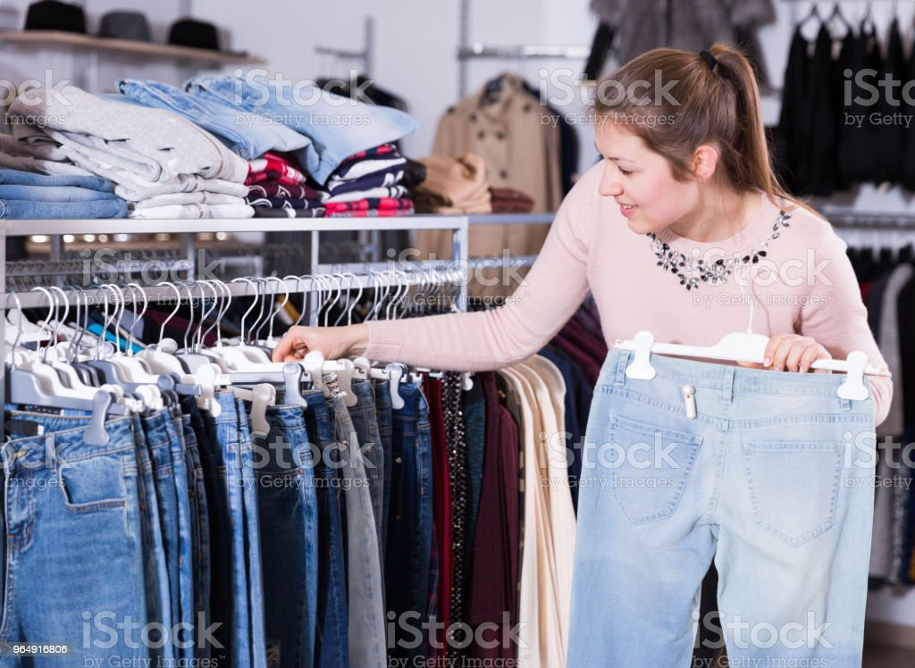 Cheerful young woman choosing stylish jeans royalty-free stock photo