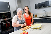 cheerful young woman cooking traditional apple pie together with elderly grandmother