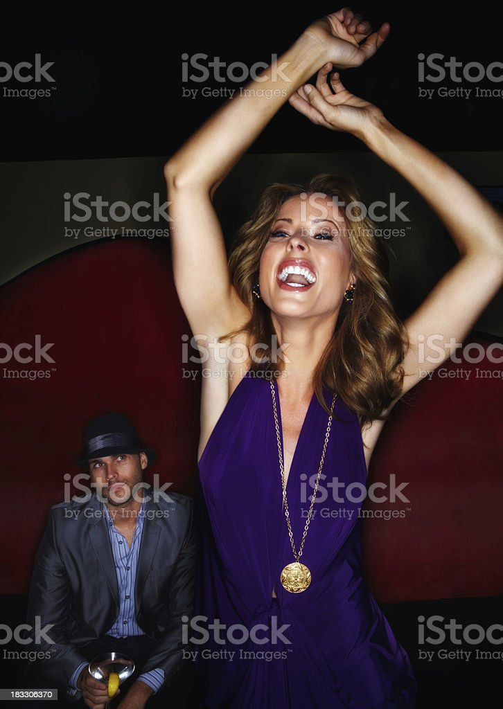 Cheerful young woman dancing and man in background stock photo