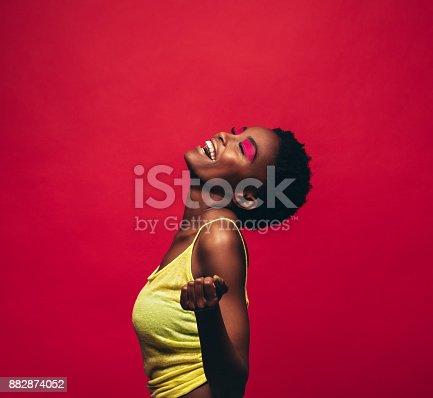 istock Cheerful young woman dancing in studio 882874052