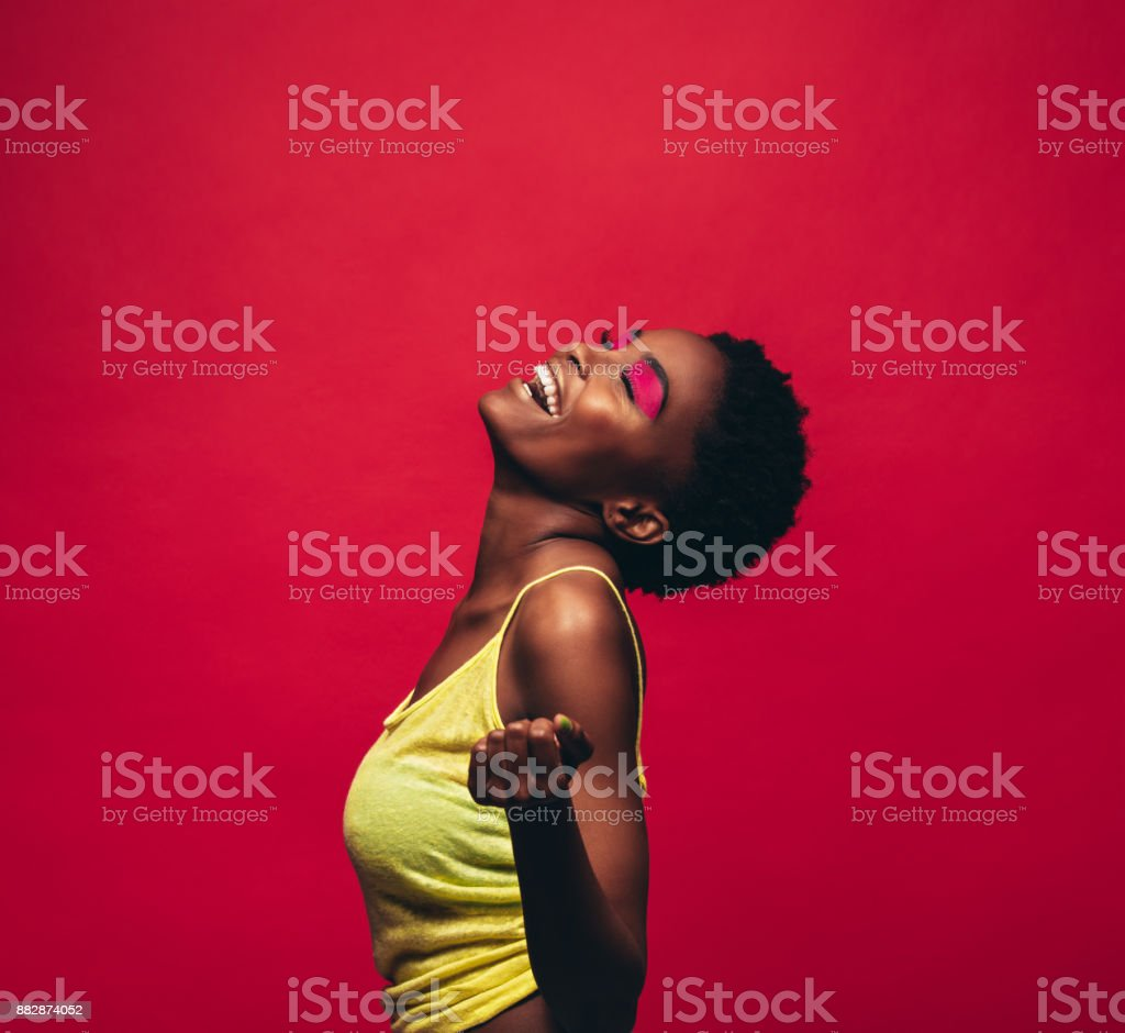 Cheerful young woman dancing in studio stock photo