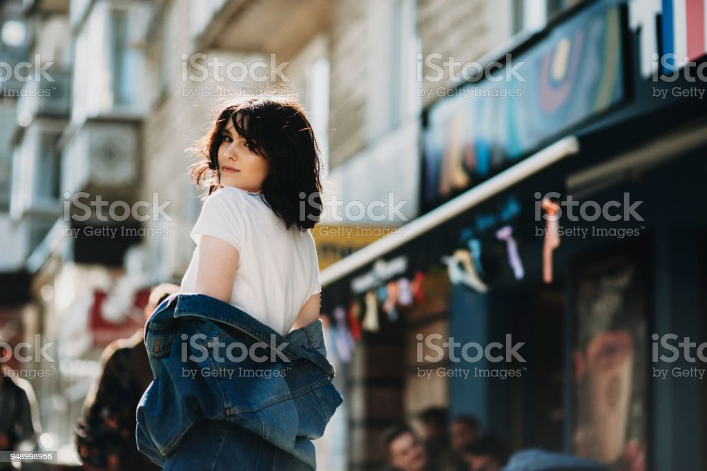Cheerful young woman, dressed in blue jeans jacket, looking over her shoulder and smiling into camera . stock photo