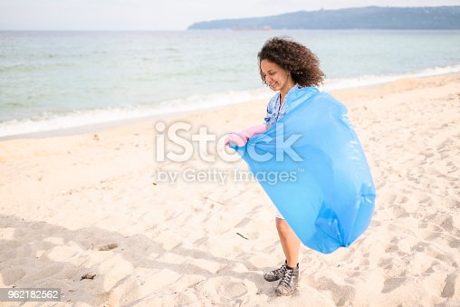 962184460 istock photo Cheerful young woman during local clean up at the beach 962182562