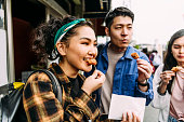 istock Cheerful young woman eating street food with friends 1204359693
