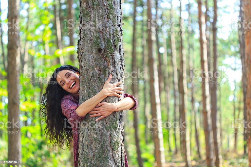 Cheerful young woman embracing a tree in the forest – Foto