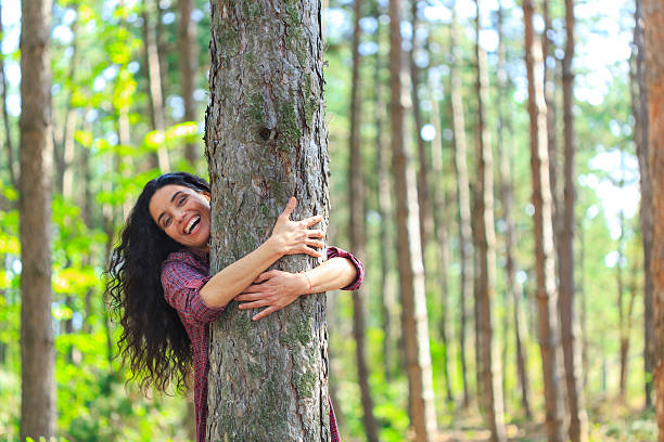 Cheerful young woman embracing a tree in the forest Playful young woman embracing a tree in the forest. Standing and looking at camera. Trees and sunbeam on background. tree hugging stock pictures, royalty-free photos & images