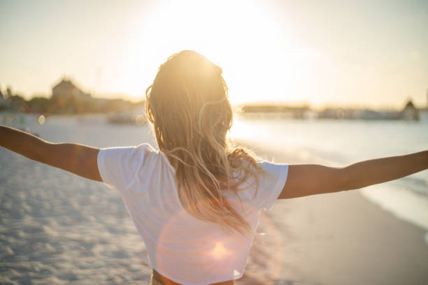 Cheerful young woman embracing nature at sunset; female standing on beach arms outstretched stock photo