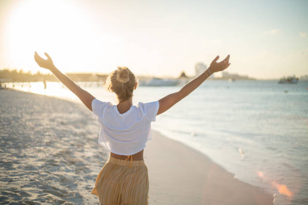 Cheerful young woman embracing nature at sunset; female standing on beach arms outstretched Cheerful young woman embracing nature at sunset; female standing on beach arms outstretched, Cancun, Mexico sun shining through dresses stock pictures, royalty-free photos & images