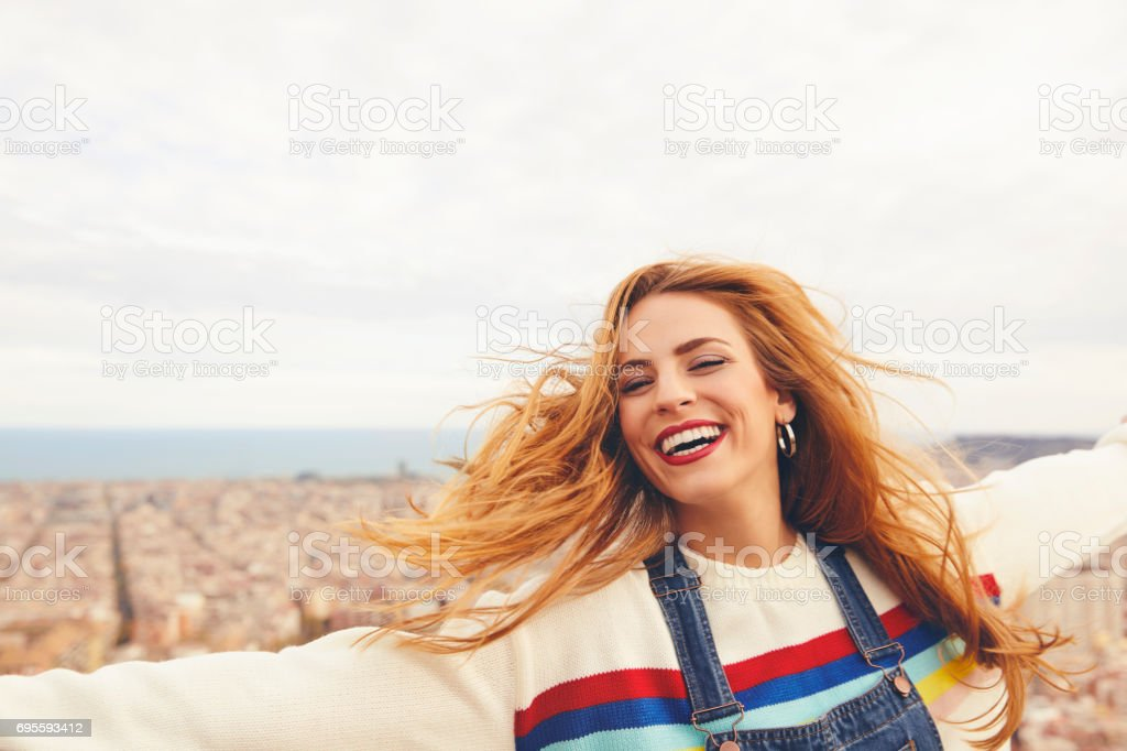 Cheerful young woman enjoying against cityscape stock photo