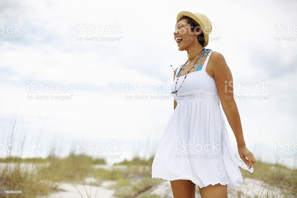 Cheerful, young woman enjoying the fresh air on beach royalty-free stock photo