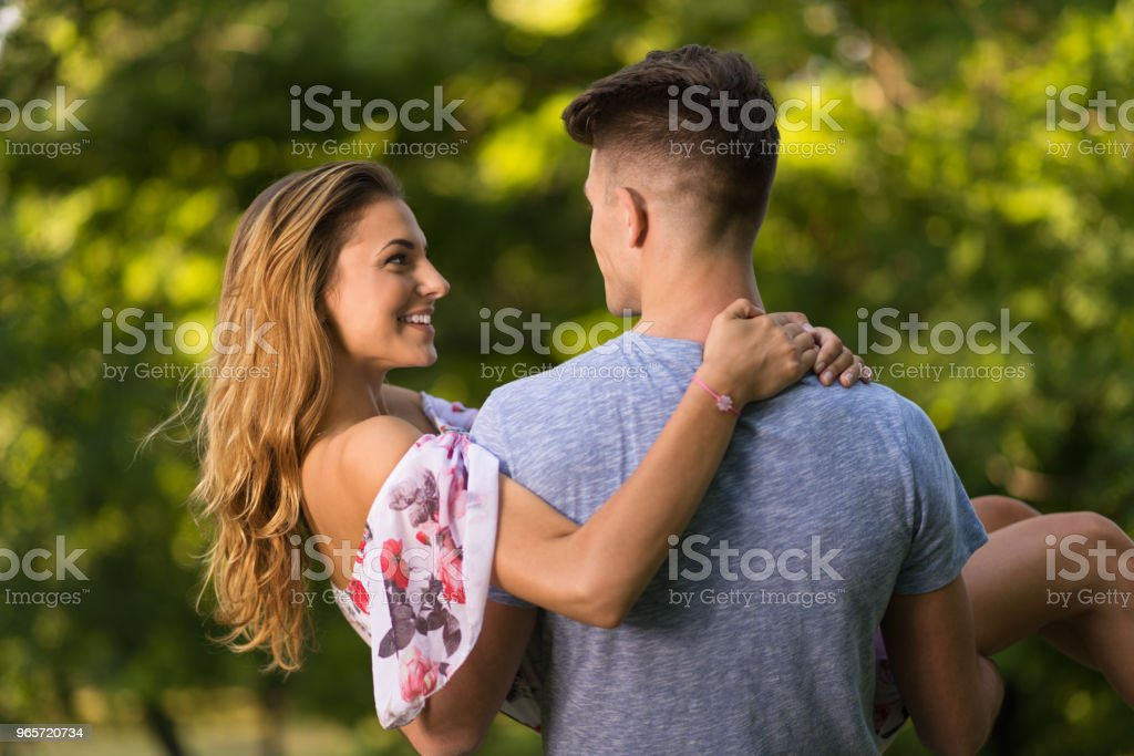 Cheerful young woman enjoying while being carried by her boyfriend. - Royalty-free Adult Stock Photo
