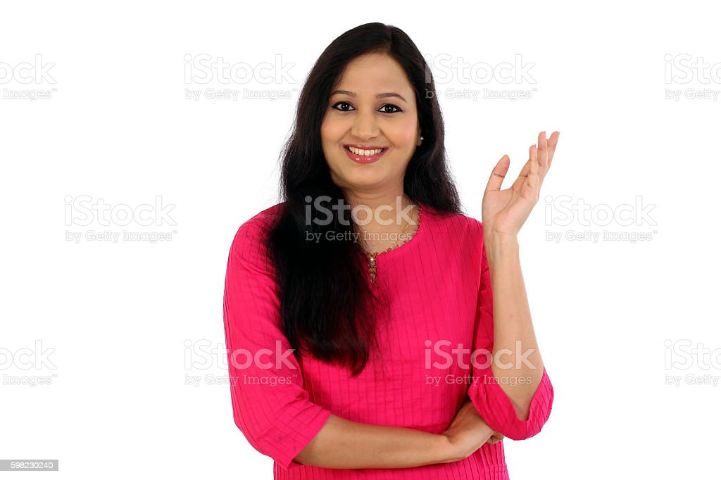 Cheerful young woman gesturing an open hand against white background foto royalty-free