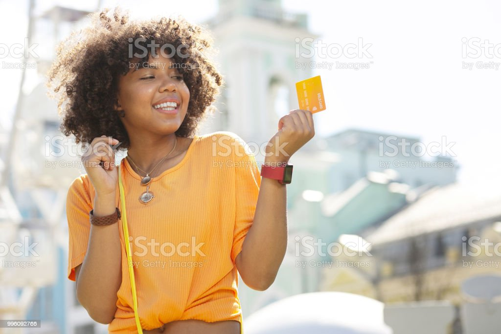 Cheerful young woman happily holding credit card stock photo