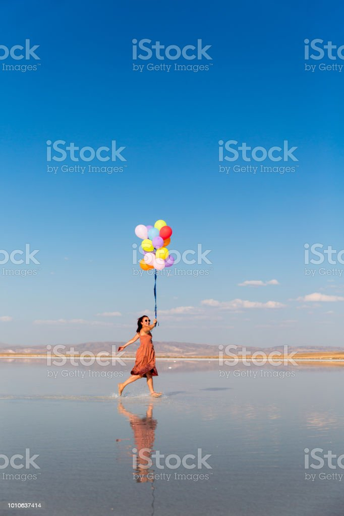 Cheerful young woman having fun with colorful balloons running stock photo