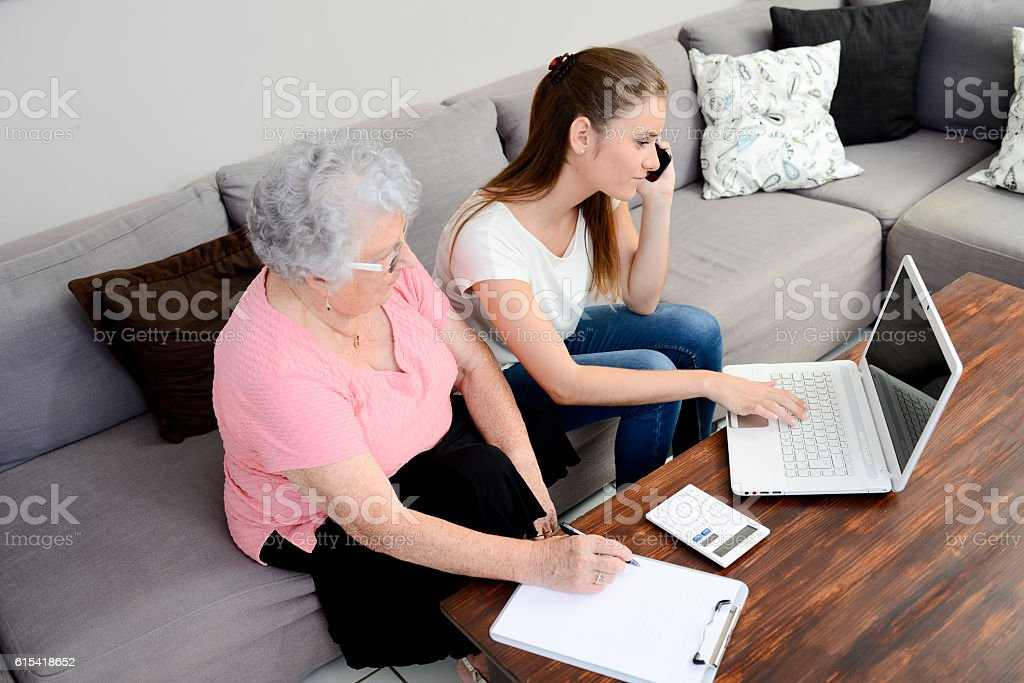 cheerful young woman helping old person paperwork and telephone call stock photo