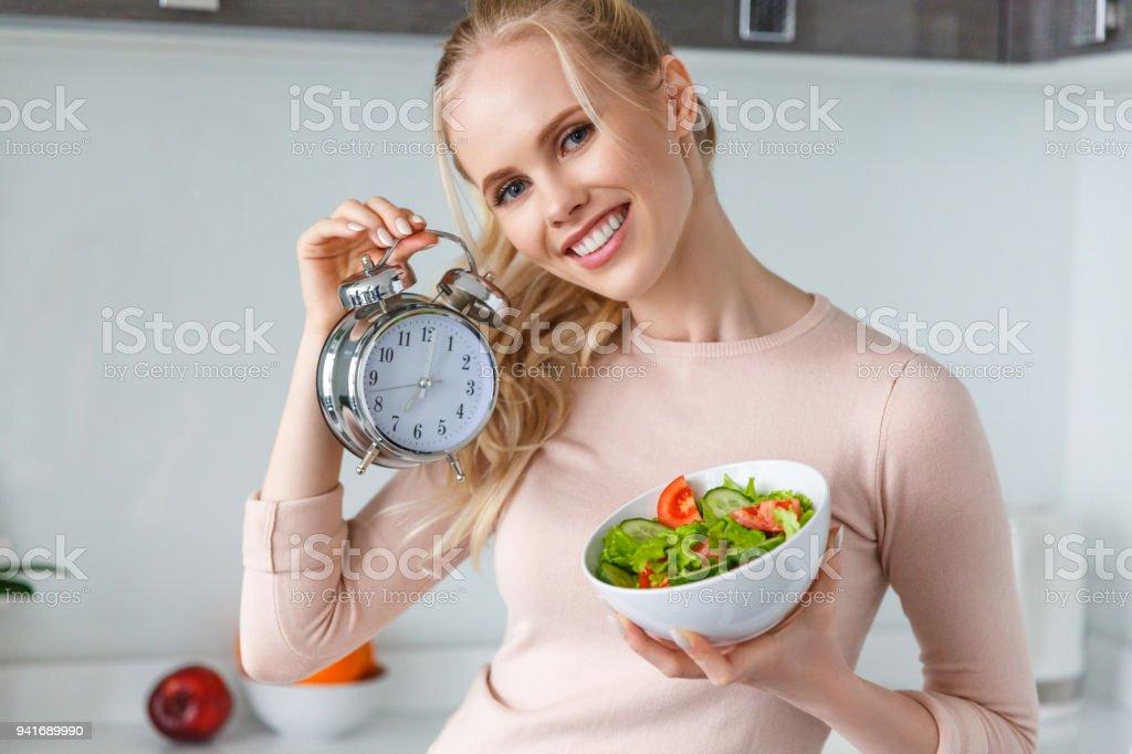 fröhliche junge Frau Holding Schüssel mit frischen, gesunden Salat und Wecker - Lizenzfrei Abgeschiedenheit Stock-Foto