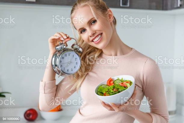 Fröhliche Junge Frau Holding Schüssel Mit Frischen Gesunden Salat Und Wecker Stockfoto und mehr Bilder von Abgeschiedenheit