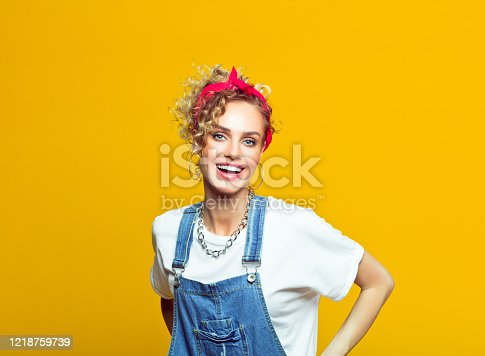 Portrait of happy young woman wearing white t-shirt, denim dungarees and red bandana smiling at camera. Studio shot on yellow background.