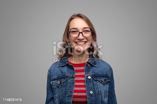 Cute young lady in stylish glasses and denim jacket cheerfully smiling and looking at camera while standing on gray background