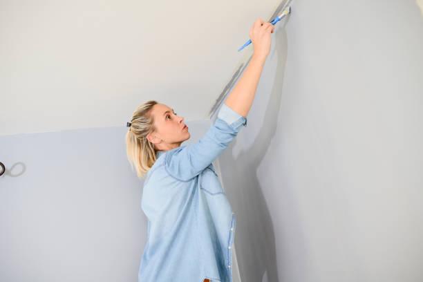 fröhliche junge frau im neuen haus malen und dekorieren ihr heim wand - französisches haus dekor stock-fotos und bilder