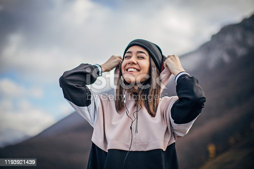 Beautiful young woman in sports clothing is listening to music.