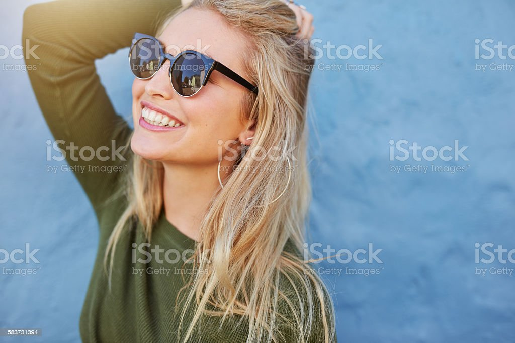 Cheerful young woman in sunglasses stock photo