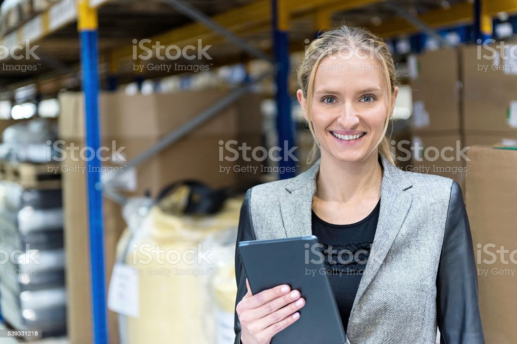 Cheerful young woman in warehouse holding tablet stock photo