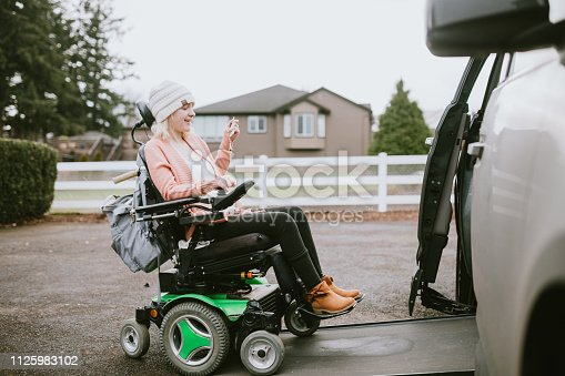 An independent young adult woman with cerebral palsy going about some of her daily routines.  She rides her wheelchair up a ramp in her specially equipped van, preparing to drive to her job.