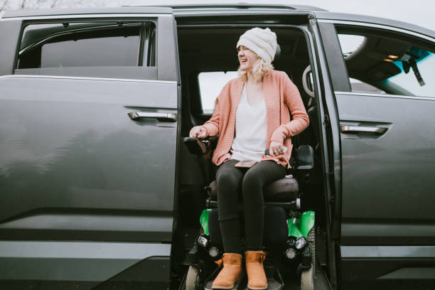 Cheerful Young Woman In Wheelchair Entering Vehicle stock photo