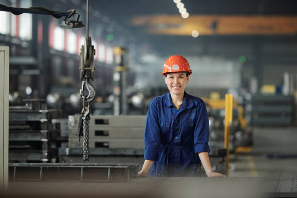 Cheerful young woman in workwear and protective helmet looking at you stock photo